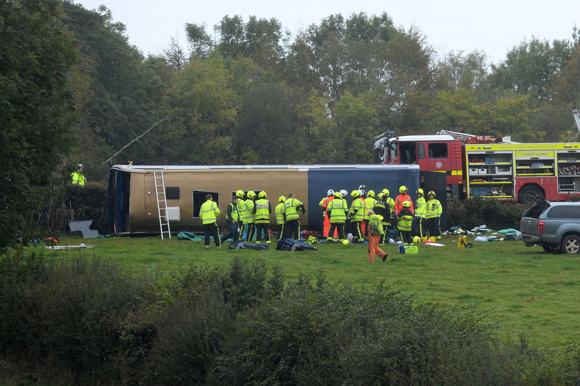 Stage coach double-decker bus comes off the road and lands on its side.