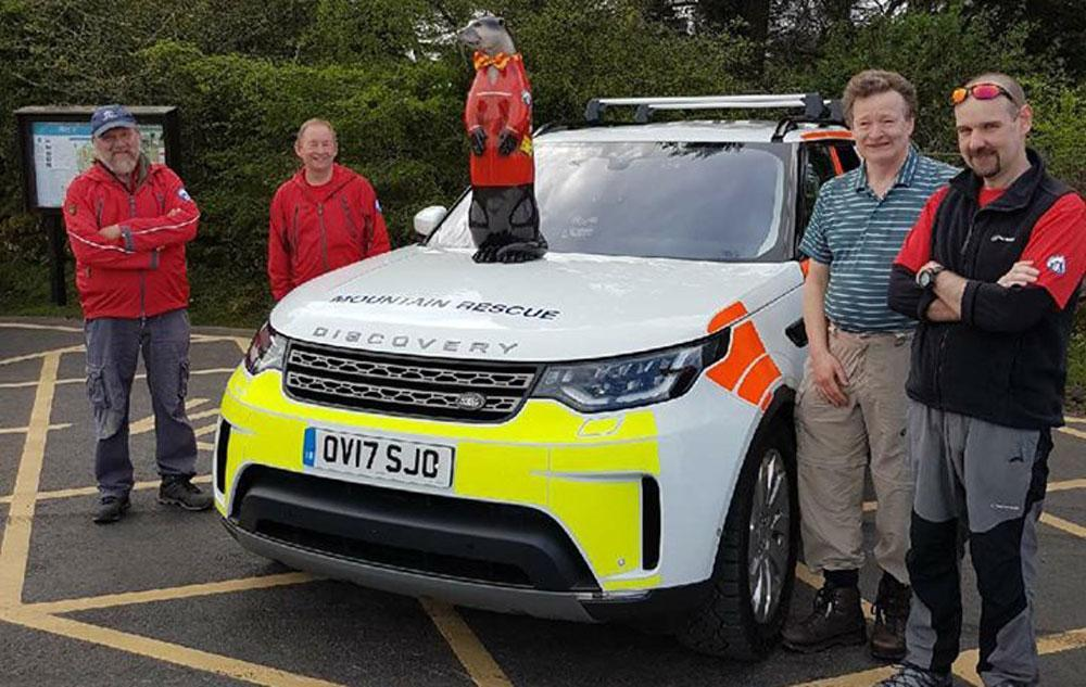 VIP Colin the Rescue Otter being greeted by his team members around the MREW Landrover Discovery